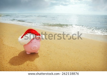 Piggy Bank with Santa hat at beach - Australian Christmas Savings - stock photo