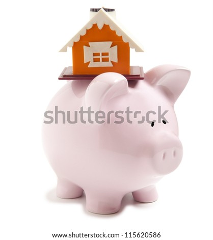 Piggy bank with small model house isolated - stock photo