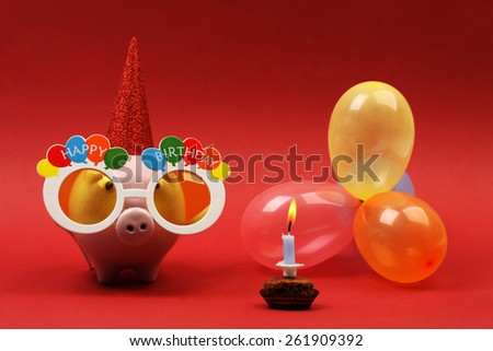Piggy bank with sunglasses Happy birthday, party hat and multicolored party balloons and birthday cake with candle on red background-horizontal - stock photo