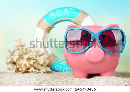 Piggy bank with sunglasses on the beach - stock photo