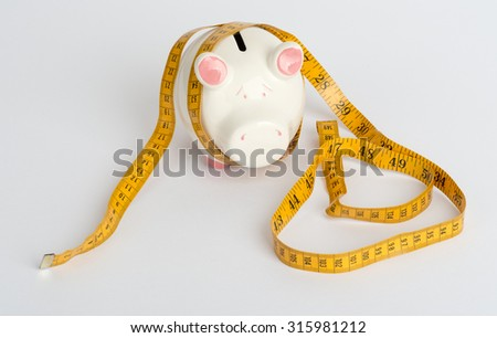 Piggy bank with tape measure on white table - stock photo