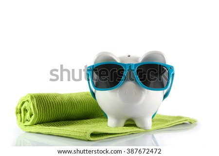 Piggy bank with towel and sunglasses, isolated on white. Holiday money concept - stock photo