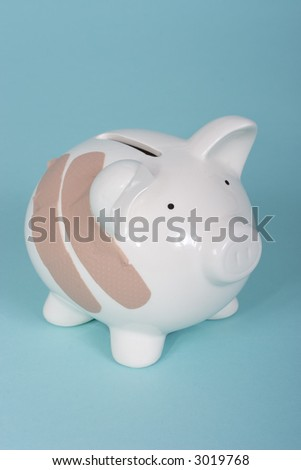 Piggy bank with two band aids - stock photo