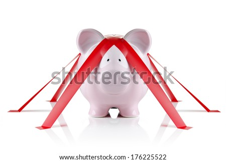 Piggy bank wrapped with red tape  - stock photo
