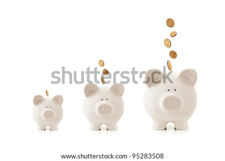 Piggy banks increasing in size, with coins falling into them.  Growing investment concept. - stock photo
