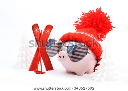 Piggy box with red hat with pompom and sunglasses shape heart with USA flag standing next to red ski and ski sticks on snow and around are snowbound trees  - stock photo