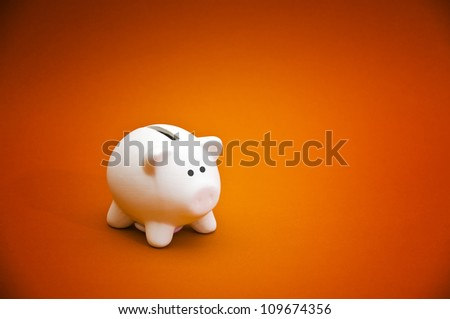 Piggy coin bank on orange background. Cute white ceramic piggy coin bank for money savings, financial security or personal funds concept. - stock photo