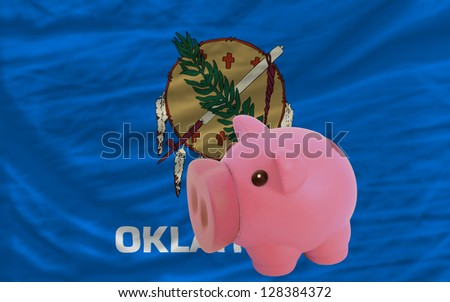 Piggy rich bank in front of flag of us state of oklahoma symbolizing saving and accumulating funds as good financial habit