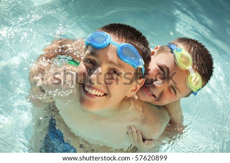 Piggybacking and laughing while at the pool - stock photo