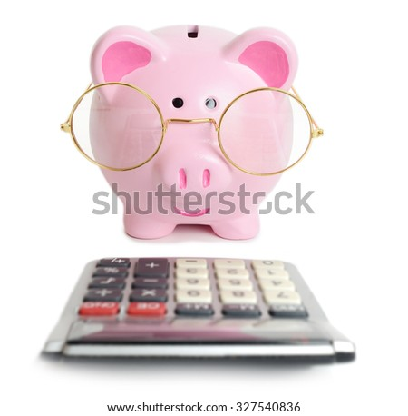 Piggybank and calculator. Isolated on white background - stock photo