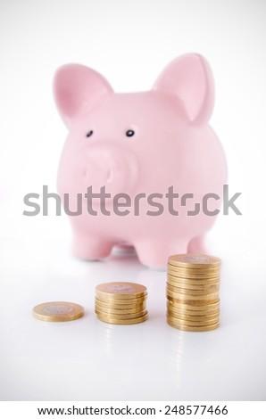 Piggybank and coins savings concept - stock photo
