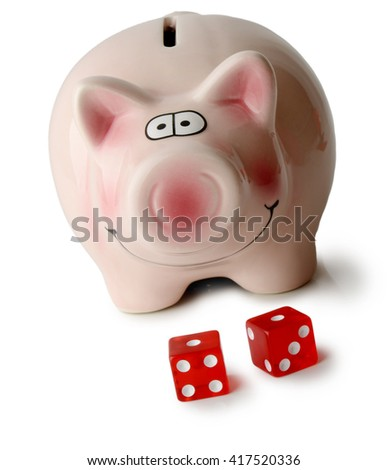 Piggybank and two red dice focuse on piggybanks eyes isolate don a white background