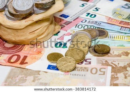 Piggybank, coins and euro bills - stock photo