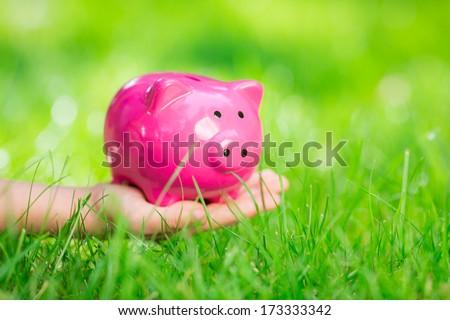 Piggybank in hand over green spring grass outdoor. Shallow depth of field - stock photo