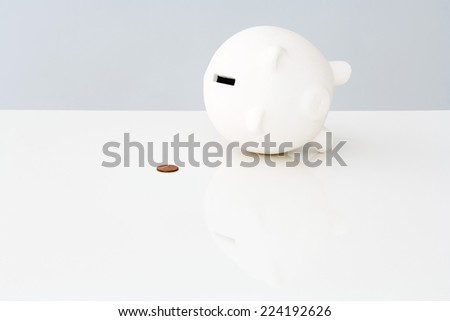 Piggybank on side next to single penny - stock photo