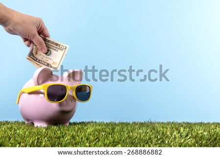 Piggybank sunglasses, grass, holiday saving money concept, copy space - stock photo