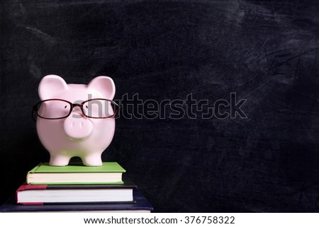 Piggybank wearing glasses, college student fees saving plan concept, copy space - stock photo