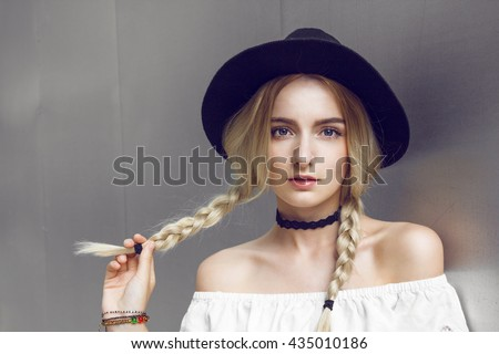 Pigtails. Close up of beautiful young blonde woman with black hat. Her hair is tied in two big ponytails. Around neck she has black choker. Professional make-up, hair style and styling.  - stock photo