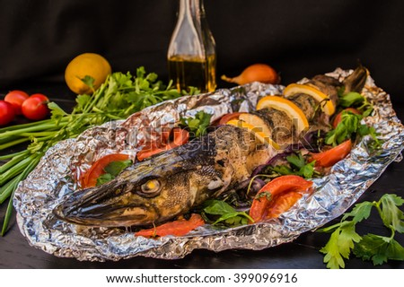 Pike baked with vegetables on the table. Wooden rustic background