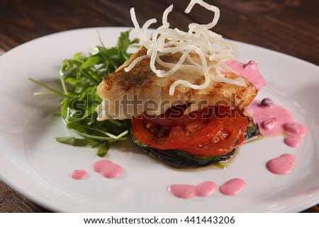 Pike with tomatoes and eggplant on plate