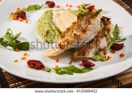 Pikeperch with mashed potatoes and with dried tomatoes on plate