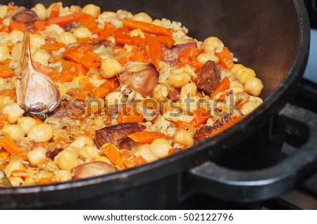 Pilaf cooked on the grill over a fire. The dish is a large metal bowl.