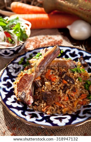 Pilaf - Rice with Lamb Chops and Vegetables. Garnished with Onions and Tomatoes Salad - stock photo