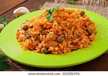 Pilaf with chicken, carrot and green peas on  plate - stock photo