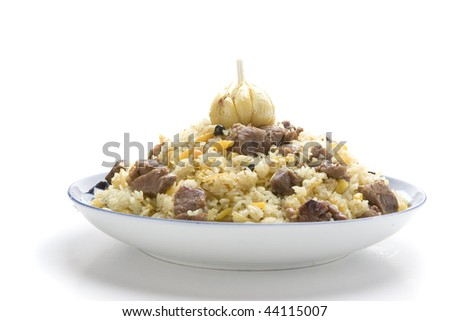 pilaf with garlic on plate on white gound - stock photo
