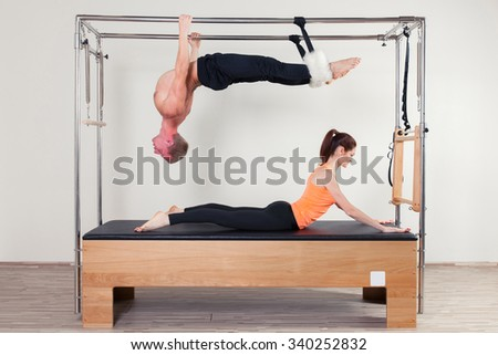 Pilates aerobic instructor woman and man  in cadillac fitness exercise. - stock photo