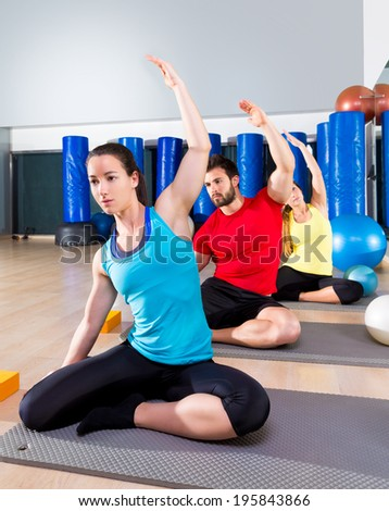 Pilates exercise the mermaid stretching obliques people group at fitness gym - stock photo