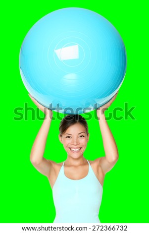 Pilates fitness woman isolated exercising with exercise ball during workout. Beautiful smiling happy mixed race Chinese Asian / Caucasian fit female fitness woman isolated cutout on green background.