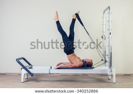Pilates reformer workout exercises man  at gym indoor. - stock photo