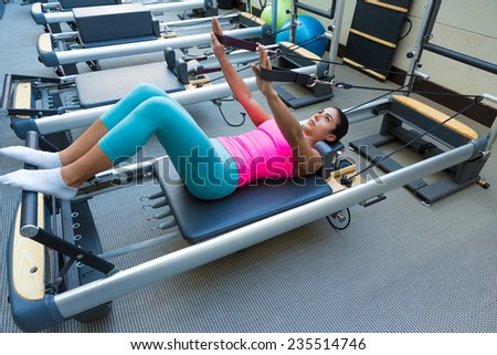 Pilates reformer workout exercises woman brunette at gym indoor - stock photo