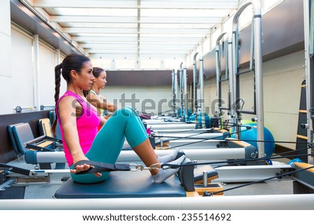 Pilates reformer workout exercises women at gym indoor - stock photo