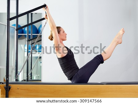Pilates woman in reformer teaser exercise at gym indoor - stock photo