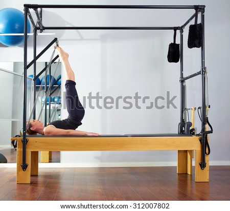 Pilates woman in reformer tower exercise at gym indoor