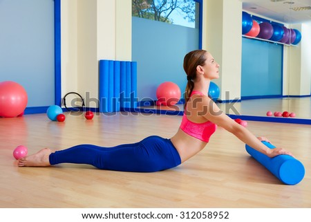 Pilates woman roller swan roll exercise workout at gym indoor