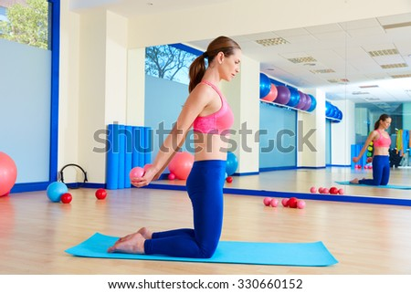 Pilates woman sand balls chest expansion exercise workout at gym indoor - stock photo