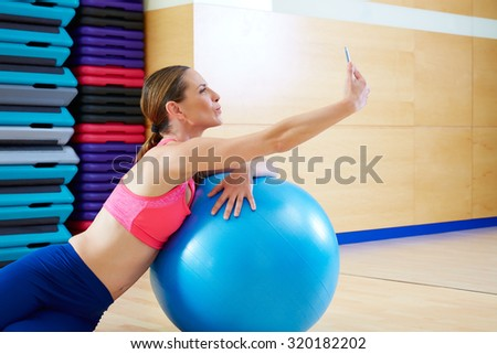 Pilates woman shoots selfie self portrait with mobile at gym relaxed with fitball - stock photo