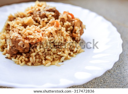 Pilau rice with lamb in a white plate on the table. - stock photo