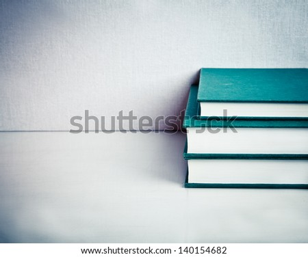 Pile composed of Tree Green Books on a white reflective table - stock photo