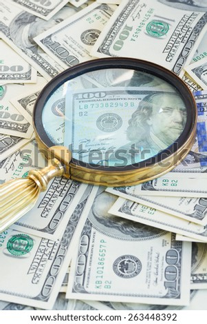 pile of american dollar bills under manifying glass - stock photo