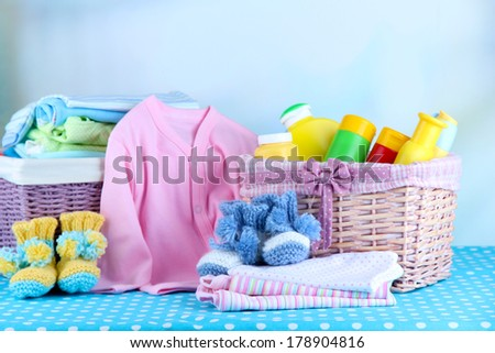 Pile of baby clothes  in basket, on table on color background - stock photo