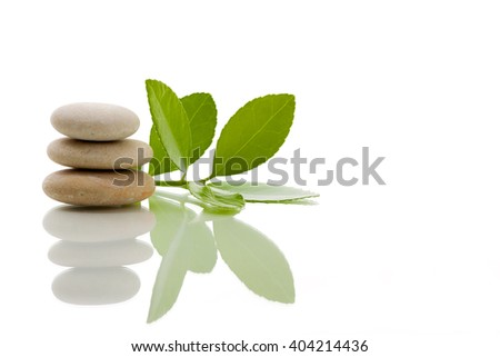 Pile of balancing pebble stones and green leaf, like ZEN stone, isolated on white background, spa tranquil scene concept with reflection