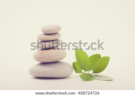 Pile of balancing pebble stones and green leaf, like ZEN stone, isolated on white background, spa tranquil scene concept with reflection, retro color pastel tone - stock photo