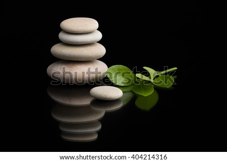 Pile of balancing pebble stones and green leaf, like ZEN stone, on black background, spa tranquil scene concept with reflection - stock photo