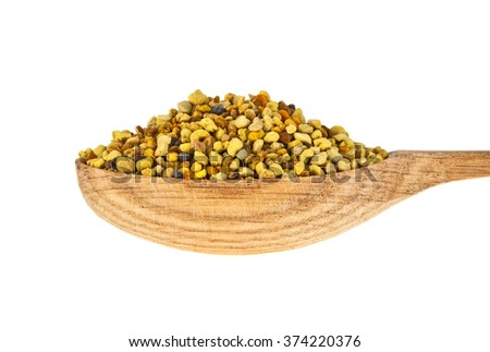 Pile of bee pollen in wooden spoon on a white background - stock photo