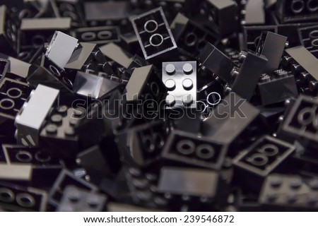 Pile of black color building blocks with selective focus and highlight on one particular block using available light. - stock photo