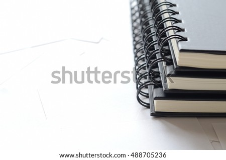 Pile of black note books on white paper with copy space for text,office supplies.